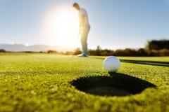L'uomo mette la palla su verde del campo da golf Fotografia Stock Libera da Diritti