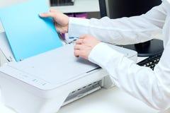 L'uomo mette la pila di carta alla stampante Fotografie Stock Libere da Diritti