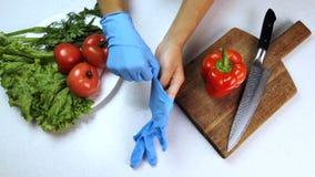 L'uomo mette sopra i guanti sulle armi dalla tavola in cui le verdure si trovano in cucina archivi video