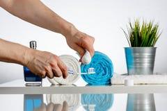 L'uomo mette sopra il dentifricio in pasta su uno spazzolino da denti Fotografia Stock Libera da Diritti