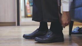 L'uomo mette sopra le scarpe costose di nuovo modo marrone con un movimento lento del cucchiaio della scarpa 3840x2160 archivi video