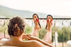 L'uomo mezzo nudo che riposa con le sue gambe ha allungato sul ferro battuto nel balcone un giorno soleggiato Fotografia Stock Libera da Diritti