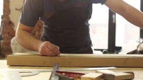 L'uomo misura la lunghezza del bordo con una misura di nastro e fa i segni della matita archivi video