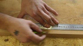 L'uomo misura la lunghezza del bordo con una misura di nastro e fa i segni della matita video d archivio