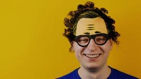 L'uomo in modo divertente e comico ride, emozioni allegramente umane divertenti, sul fondo giallo della parete, capelli neri ricc video d archivio