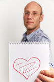 L'uomo mostra l'organizzatore del taccuino con cuore Fotografia Stock