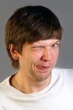 L'uomo mostra la lingua e sbatte le palpebre Fotografia Stock
