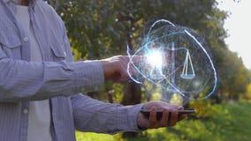 L'uomo mostra l'ologramma con le scale dell'equilibrio stock footage