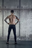 L'uomo muscolare allegro adatto sta di nuovo alla macchina fotografica Immagini Stock Libere da Diritti