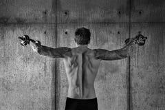 L'uomo muscolare allegro adatto sta di nuovo alla macchina fotografica con peso Immagine Stock