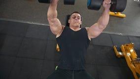 L'uomo muscolare bello fa gli esercizi delle teste di legno in una palestra archivi video