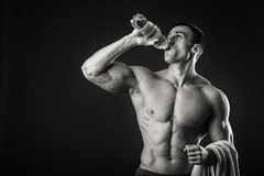L'uomo muscolare beve l'acqua su un fondo scuro Immagini Stock