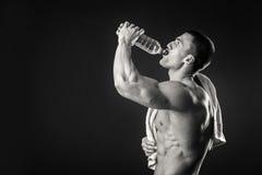L'uomo muscolare beve l'acqua su un fondo scuro Fotografia Stock