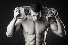 L'uomo muscolare beve l'acqua su un fondo scuro Fotografia Stock Libera da Diritti