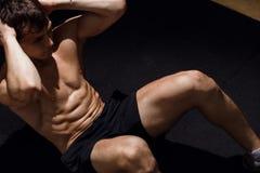 L'uomo muscolare che esercita fare si siede sull'esercizio Atleta con gli addominali scolpiti Immagini Stock Libere da Diritti