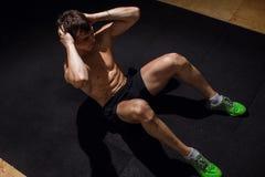 L'uomo muscolare che esercita fare si siede sull'esercizio Atleta con gli addominali scolpiti Immagini Stock