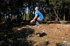 L'uomo muscolare che fa il salto di allenamento su nell'esercizio di aria in abiti sportivi d'uso dello sportivo bello della fore Fotografie Stock Libere da Diritti