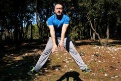 L'uomo muscolare che fa il salto di allenamento su nell'esercizio di aria in abiti sportivi d'uso dello sportivo bello della fore Immagini Stock Libere da Diritti