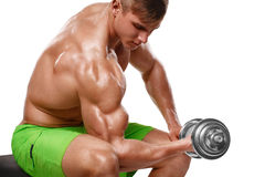 L'uomo muscolare che risolve fare si esercita con le teste di legno ai bicipiti, forte torso nudo maschio, isolato sopra fondo bi Fotografia Stock Libera da Diritti