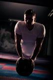 L'uomo muscolare che si esercita facendo spinge aumenta Immagini Stock