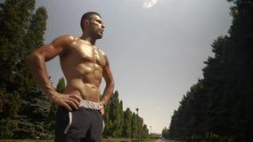L'uomo muscolare di misura del costruttore di corpo prende una rottura durante risolve all'aperto video d archivio