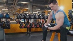 L'uomo muscolare fa gli esercizi delle teste di legno nella stanza di allenamento Fotografie Stock