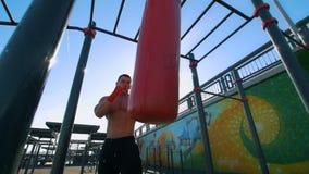 L'uomo muscolare si è impegnato nel pugilato con il punching ball di estate all'aperto, rallentatore video d archivio