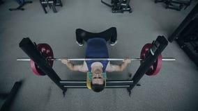 L'uomo muscolare solleva i pesi Colpo del grandangolo stock footage