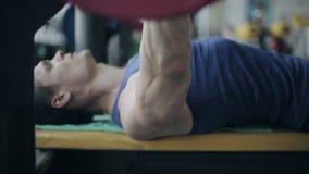 L'uomo muscolare solleva i pesi r video d archivio