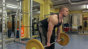 L'uomo muscolare solleva un bilanciere pesante in una palestra archivi video
