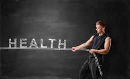 L'uomo muscolare tira la corda con la parola & il x27; health& x27; Immagini Stock Libere da Diritti