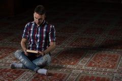 L'uomo musulmano sta leggendo il Corano Fotografia Stock