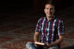 L'uomo musulmano sta leggendo il Corano Fotografia Stock Libera da Diritti