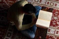 L'uomo musulmano sta leggendo il Corano Immagine Stock