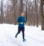 L'uomo negli sport blu indossa il funzionamento nella foresta fotografia stock