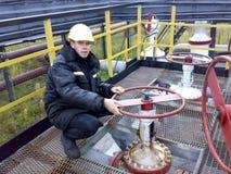 L'uomo nei camici di Rosneft L'operatore gira il volante della valvola sulla conduttura immagini stock