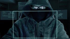 L'uomo nei vetri del cappuccio e nella maschera della passamontagna si siede al computer portatile del computer ed ai dati di seg archivi video