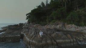 L'uomo nel bianco sulla spiaggia del tramonto in Tailandia oscilla video d archivio