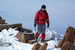 L'uomo nel colore rosso viaggia in montagne Immagine Stock