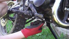 L'uomo nel cortile fissa una vite in suo motociclo con uno strumento stock footage
