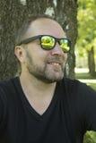 L'uomo nel parco in occhiali da sole Immagini Stock Libere da Diritti