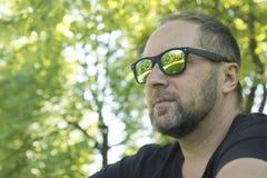 L'uomo nel parco in occhiali da sole Fotografia Stock Libera da Diritti
