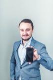 L'uomo nel rivestimento e con una barba che giudica un telefono disponibile Immagini Stock Libere da Diritti