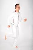 L'uomo nel vestito bianco di sport funziona a piedi nudi Fotografie Stock