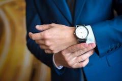 L'uomo nel vestito blu esamina il suo orologio Fotografia Stock Libera da Diritti