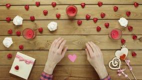 L'uomo nell'amore con cuore di carta si siede dalla tavola di legno, vista superiore video d archivio