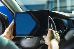 L'uomo nell'automobile, con la compressa in mani Fotografia Stock Libera da Diritti