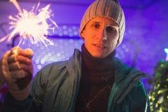 L'uomo nell'inverno copre la stella filante bruciante della tenuta sulla notte di San Silvestro Immagini Stock