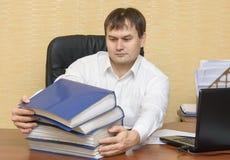 L'uomo nell'ufficio tira a se stesso le cartelle con i documenti Fotografie Stock Libere da Diritti
