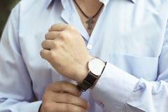 L'uomo nella camicia blu-chiaro indossa un orologio luxary Immagini Stock Libere da Diritti